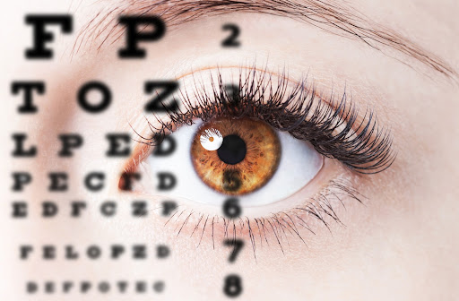 Up-close view of an eye looking into the distance at an eye chart.